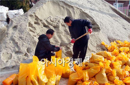 강진군은 신속한 제설작업을 위해 강진군청 직원들이 유관기관 및 11개 읍,면에 배부할 모래주머니 300장을 담고 있다.