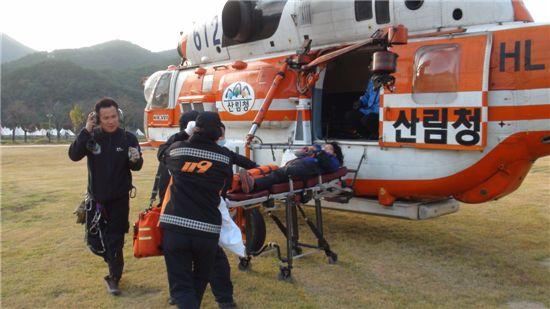산림헬기가 유씨를 구조, 119구급대에 인계하고 있다.