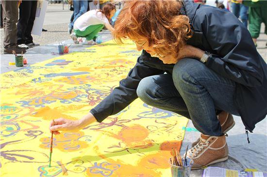지난 6월 정신대문제대책협의회가 주관한 유럽평화기행 '나비의 꿈' 프로젝트에서 한 외국인 여성이 나비 걸개그림 그리기 행사에 참여하고 있다.