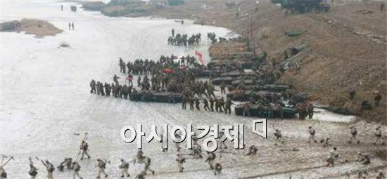 북한군이 도하훈련을 벌이고 있다.설상복을 입은 스키부대 뒤로 군인들이 뜰다리를 옮기고 있다.