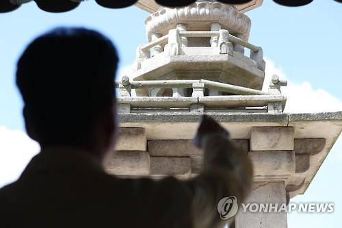 2016년 9월 12일 경주에서 발생한 규모 5.8 지진에 떨어진 다보탑 난간석을 가리키는 관계자. [사진출처=연합뉴스]