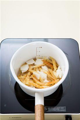 3. 냄비에 참기름과 식용유를 두르고 북어채와 무를 넣어 3분 정도 볶다가 고춧가루를 넣어 볶는다. 고춧가루가 볶아져 고소한 맛이 나면 물 3컵을 넣어 10분 정도 끓인다.