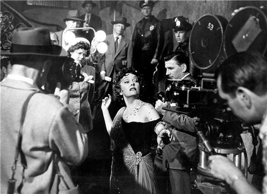 살로메의 일곱 베일의 춤을 연상시키는 요염한 자태로 계단을 내려오는 노마는 카메라 앞에서 '말'이 필요 없었던 시대의 아우라를 한껏 발산하며 혼신의 연기를 펼친다. 그런 그녀에게 이 카메라가 영화 카메라인지, 살인 용의자를 찍는 취재 카메라인지는 중요하지 않다.