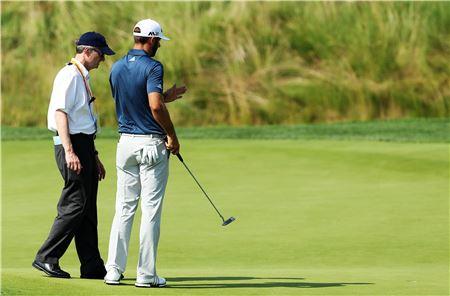 """2019년 1월부터 """"보다 쉽고, 빠르게, 공평하게"""" 만든 새로운 골프규칙이 적용된다. 더스틴 존슨이 지난해 US오픈 최종일 5번홀 그린에서 경기위원에게 공이 움직인 상황을 설명하는 모습."""