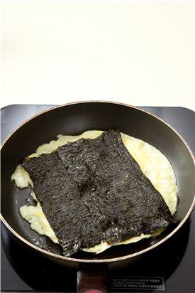 3. 팬을 달구어 식용유를 두르고 불을 약하게 줄여 달걀물의 1/3만 붓고 반으로 접어 잘라둔 김을 얹고 익기 시작하면 끝 쪽에서부터 접어 돌돌 만다.