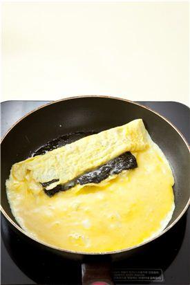 4. 어느 정도 말아졌으면 달걀의 끝 부분을 위로 살짝 들고 식용유를 약간 더 두르고 남은 달걀물을 부어 남은 김 반 장을 얹고 살짝 더 익힌다.