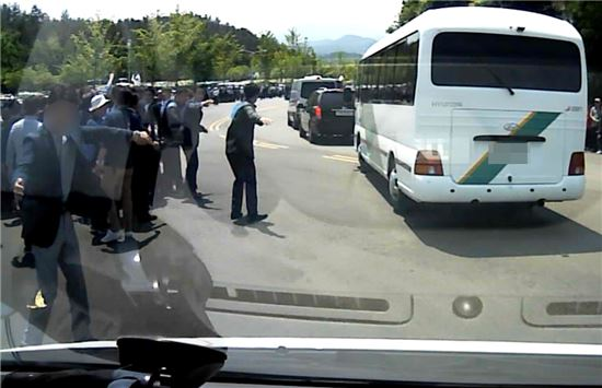 18일 오전 광주 북구 운정동 국립 5·18민주묘지 진출입로에서 응급환자를 실은 119구급차가 청와대 경호원들의 도움을 받으며 병원으로 이동하고 있다. 사진 = 광주 북부소방서