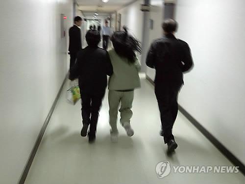 2014년 8월 경북 칠곡에서 의붓딸을 때려 숨지게 한 혐의(상해치사 등)로 구속기소된 계모 임모(36)씨가 취재진을 피해 선고공판이 열리는 법정으로 가고 있다. [이미지출처=연합뉴스]