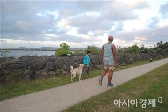 ▲통가의 한 시민이 아이와 함께 바닷가를 산책하고 있다.