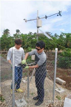 ▲바이니 지역에서 신용희(왼쪽), 김광형 박사가 강수량 측정장치를 교체하고 있다.