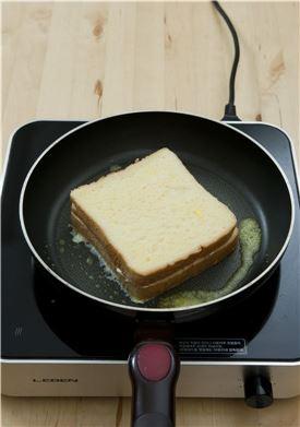 5. 팬을 달구어 버터를 적당량 두르고 식빵을 넣어 앞뒤를 노릇하게 구운 후 크림치즈가 말랑해지도록 은근한 불로 굽는다.