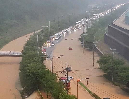 부산지역에 호우경보가 내려진 11일 오전 부산 강서구 지하과학산단로 일대 도로가 인근 하천이 범람해 차량이 통제되고 있다. [이미지출처=연합뉴스]
