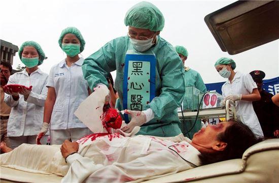 체포된 파룬궁 수련자들의 생체 장기적출을 시연하고 있는 파룬궁수련자들. 사진 = 연합뉴스/AP