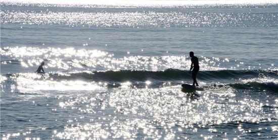 은빛 물결 헤치며 서핑을 즐기는 서퍼