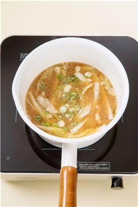 4. 날콩가루를 넣고 대파와 다진 마늘을 넣은 다음 소금으로 간을 한다.