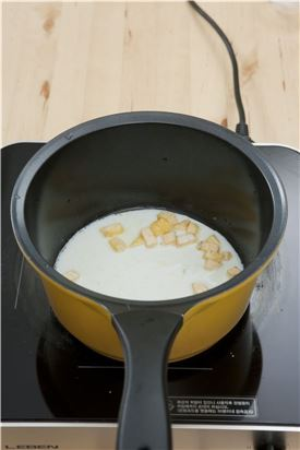 4. 냄비에 버터를 두르고 고구마를 넣어 볶다가 우유 1+1/2컵과 설탕, 계핏가루를 넣어 주걱으로 저어가며 졸인다.