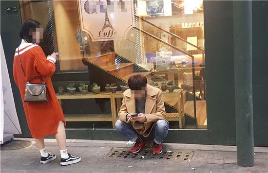 7일 명동의 한 상점 입구 옆에서 외국인 관광객이 담배를 피우고 있다.