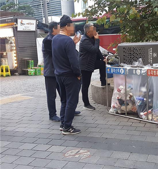 7일 명동에서 외국인 관광객들이 흡연을 하고 있다. 바닥엔 금연구역을 알리는 표식의 칠이 벗겨져 있다.