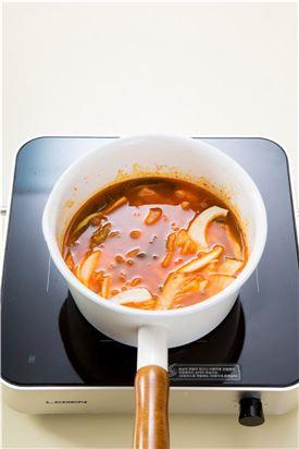 3. 5분 정도 지나 재료가 어느 정도 익으면 다시마 우린 물과 김치 국물을 부어 센 불에서 끓이다가 국물이 끓으면 중간 불에서 15분 정도 푹 끓인다.