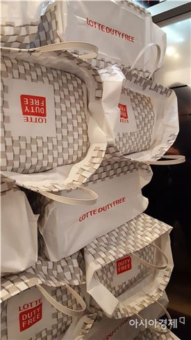 롯데면세점 본점에서 한 중국인 보따리상이 화장품이 든 비닐 가방을 키 높이 이상으로 쌓아 엘리베이터에 탄 모습.(아시아경제 DB)