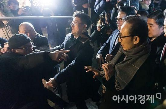 """이명박 전 대통령이 18일 서울의 한 음식점에서 열린 친 이계 송년 모임에 참석하는 도중 """"이명박 구속""""을 외치던 한 시민으로부터 거센 항의를 받고 있다./윤동주 기자 doso7@"""