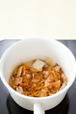 5. 냄비에 식용유를 두르고 양념한 돼지고기를 넣어 볶다가 배추김치와 무를 넣어 볶는다.