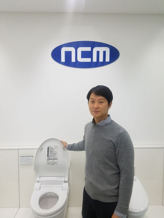김형중 엔씨엠 대표가 비데 신제품 옆에서 포즈를 취하고 있다.