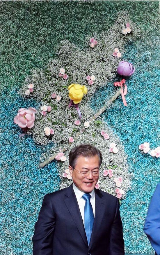 문재인 대통령이 17일 오후 서울 삼성동 그랜드 인터컨티넨탈에서 열린 한반도 안정과 평화를 위한 기원 법회에서 한반도 평화를 기원하며 한반도 모형판에 연꽃을 부착한 뒤 내려오고 있다. [이미지출처=연합뉴스]