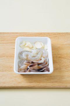 2. 오징어는 껍질째 내장을 빼내고 링으로 썰고 새우는 깨끗하게 손질한다.마늘은 편으로 썬다.