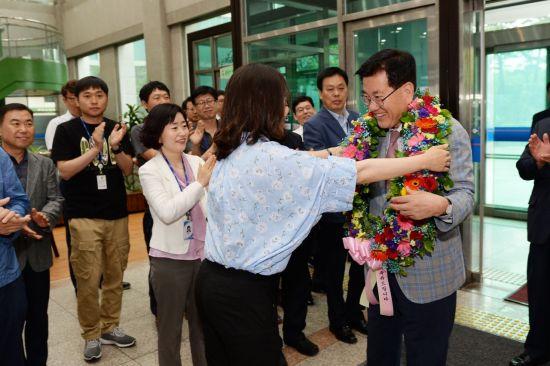 유덕열 동대문구청장이 14일 출근길에 직원들의 꽃다발을 받고 즐거워하고 있다.