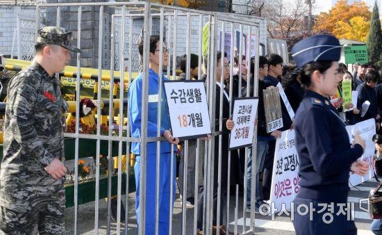 5일 서울 용산구 국방부 앞에서 열린 양심적 병역거부 징벌적 대체복무제안 반대 긴급 기자회견에서 참여연대를 비롯한 시민사회단체 관계자들이 퍼포먼스를 하는 가운데 군인들이 그 앞을 지나고 있다./김현민 기자 kimhyun81@