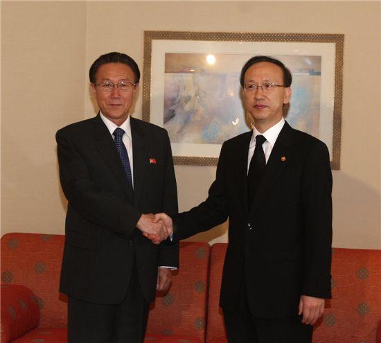 현인택 통일부 장관과 김양건(왼쪽) 북한 노동당 통일전선부장이 악수를 나누고 있다.
