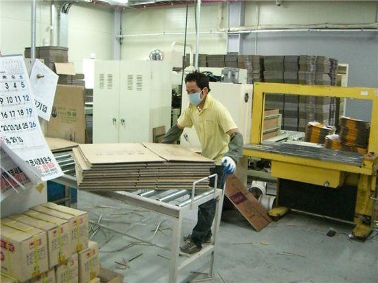 박스 업체 한 직원이 골판지 상자를 밴딩 기계로 묶고 있다. [사진=아시아경제DB]