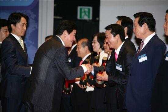 이제학 양천구청장(오른쪽)이 최경환 지식경제부장관으로 부터 상패를 받고 즐거워하고 있다.