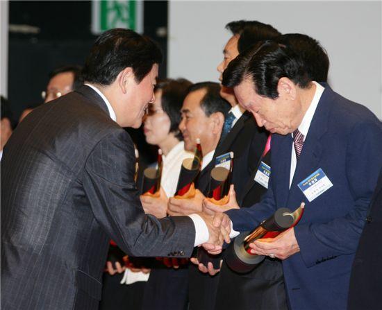 김평전 마포구시설관리공단 이사장(오른쪽)이 최경환 지식경제부장관으로 부터 상패를 받고 있다.