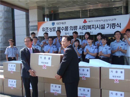 대전사회복지공동모금회에 위조상표 몰수품 옷을 전하고 있는 대전세관 관계자들.