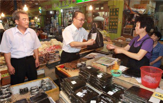 추석을 앞둔 17일 오후 박재완 고용노동부 장관이 서울 황학동 중앙시장을 방문, 전통시장 상품권으로 김을 구입하고 있다