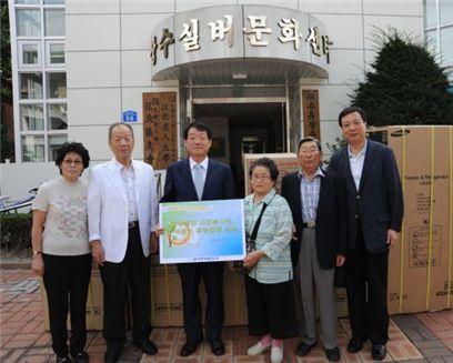 후원물품 전달후 관계자들과 기념 촬영하는 남인석 사장(가운데)