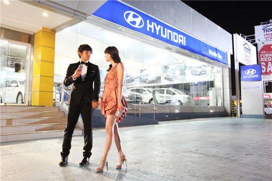 필리핀 마닐라베이에서 현지 촬영 중인 드라마 '도망자 플랜 비(Plan B)'의 주인공 비(정지훈)와 이나영이 현지 현대차 대리점을 배경으로 연기하고 있는 모습.