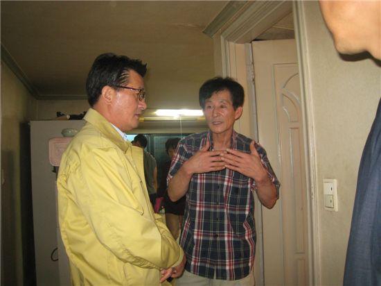 유종필 관악구청장(왼쪽)이 수해 피해 주민으로부터 피해 상황을 설명듣고 있다.
