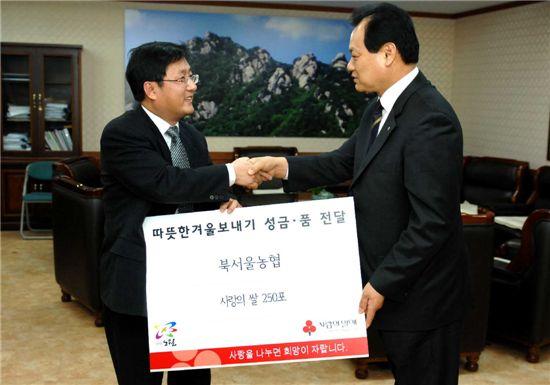 김성환 노원구청장이 최건빈 북서울농협조합장으로부터 사랑의 쌀 250포를 받고 감사의 뜻을 전하고 있다.