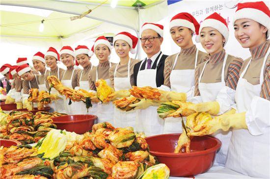 산타 복장을 한 아시아나항공 윤영두 사장(가운데)과 승무원들이 2일 강서구 오쇠동 본사에서 '사랑의 김장 담그기'행사를 가지고 있다.