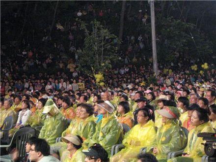 故 노무현 전 대통령 서거 2주기를 이틀 앞둔 21일 김해 봉하마을, 김제동의 토크콘서트를 관람하기 위해 행사장 가득 모여든 시민의 모습. 준비된 2000여석이 부족해 앉을 곳이 없자 추모객들은 봉하산 자락과 잔디밭에도 자리를 잡았다.