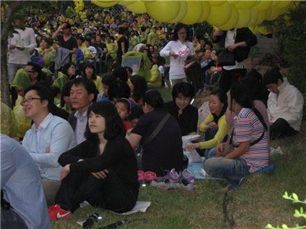 故 노무현 전 대통령 서거 2주기를 이틀 앞둔 21일 김해 봉하마을, 김제동의 토크콘서트를 관람하기 위해 행사장 가득 모여든 시민의 모습. 준비된 2000여석이 부족해 앉을 곳이 없자 추모객들은 돗자리를 깔고 잔디밭에 자리를 잡았다.