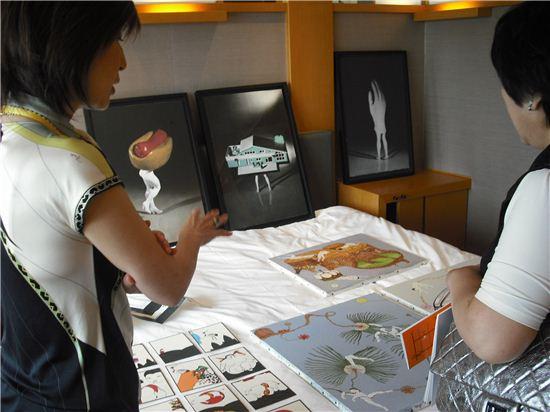 호텔아트페어가 열리고 있는 객실 침대위 작품들을 보고 이야기를 나누는 일본의 한 갤러리 관계자와 관람객 모습.