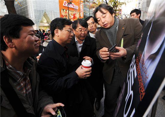 중국 최대 이동통신사 차이나모바일의 리 웨 총재(왼쪽에서 두번째)가 명동 NFC존에 방문해 설명을 듣고 있다.