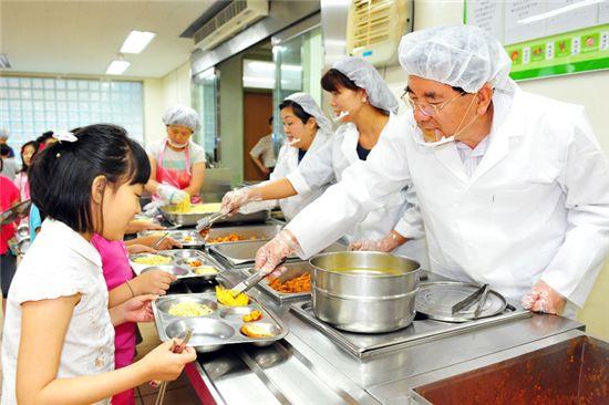 유덕열 동대문구청장이 휘경초등학교에서 아이들에게 무상급식 배식을 하고 있다.