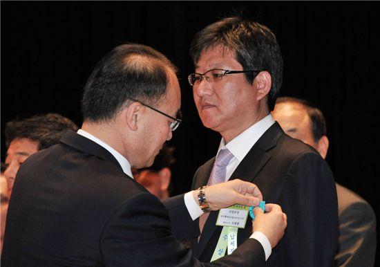 ▲조태휘 바이엘 머티리얼사이언스 대표(오른쪽)가 박재완 기획재정부 장관으로부터 산업포장을 받고 있다.