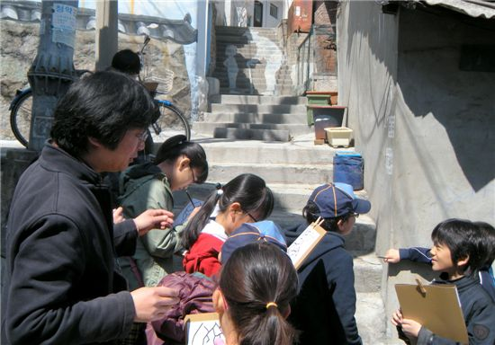 성북구 어린이 마을아카데미에 참여 중인 서울 동신초등학교 4~5학년 학생들이 장수마을 속 숨은그림찾기를 통해 '나만의 지도'를 만들고 있는 모습과 어린이들이 그려 넣은 지도들.