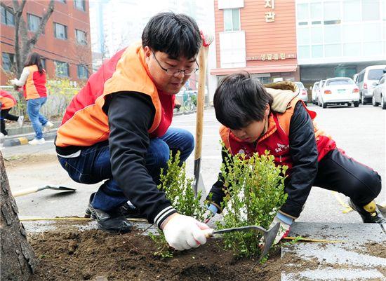 서울 성동구 마장동 성동종합사회복지관에서 SK건설 봉사활동 참가자들이 화단에 나무를 옮겨심고 있다.